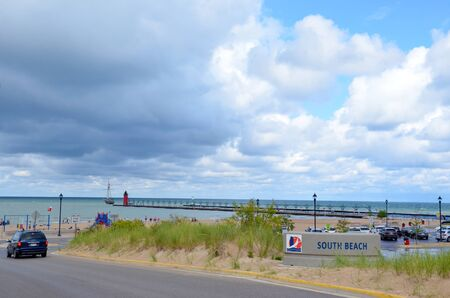 SOUTH HAVEN, MI  USA - AUGUST 12, 2017: Visitors arrive at outh Haven beach on Lake Michigan, with the lighthouse in the background.