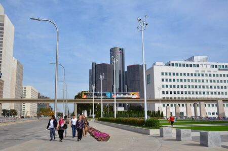 DETROIT, MI  USA - OCTOBER 21, 2017:  Women walk along Jefferson Avenue near Cobo Hall in downtown Detroit, with the Renaissance Center in the background.