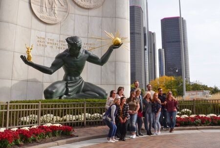 DETROIT, MI  USA - OCTOBER 21, 2017:  Tourists pose in front of Spirit of Detroit sculpture in downtown Detroit.