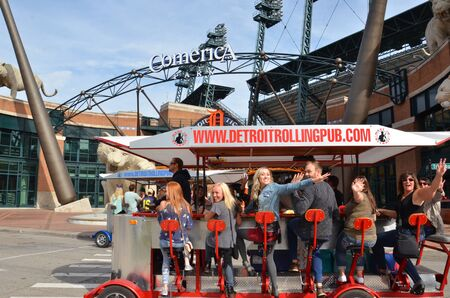 DETROIT, MI  USA - OCTOBER 21, 2017:  Visitors wave from Detroit Rolling Pub outside Comerica Park.