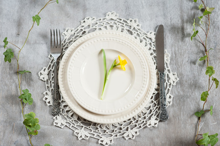 Serving plate, knife and fork on a table with a narcissist photo