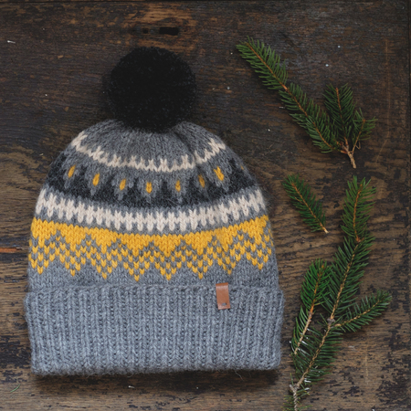 tejido de lana: Gray knitted hat with a pompon on a wooden background Foto de archivo
