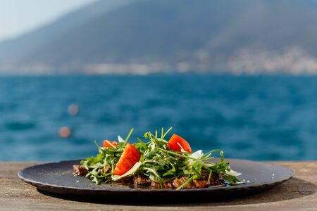Veal steak salad with arugula, lettuce, halves of small cherry tomatoes, Parmesan cheese on the background of the sea