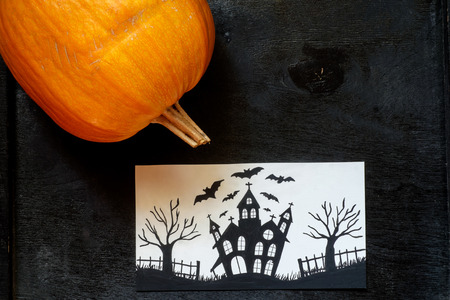 Halloween pumpkin on a black wooden background with a card Stock Photo