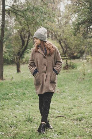 Outdoors lifestyle fashion portrait of pretty young woman walking on the autumn park.