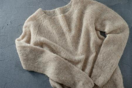 Pastel beige knitted woolen sweater on a hanger Stock Photo