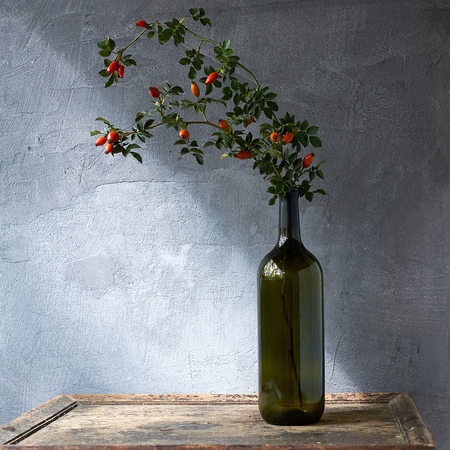 bottle with a rose hip on a gray and wooden background