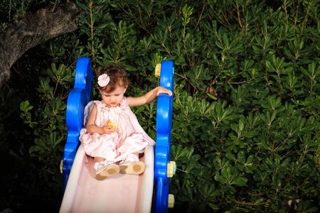 kid sitting on a slide looking a lemon
