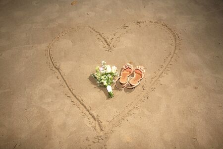 shoes and bouquet on a heart made on sand