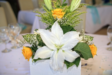 Composition of flowers at wedding reception with table set on background photo