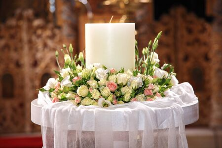 close-up of flowers and a big candle on a greek wedding photo