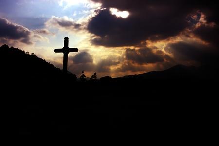 tumba de jesus: cruz y el dios sol en el cielo nublado Foto de archivo