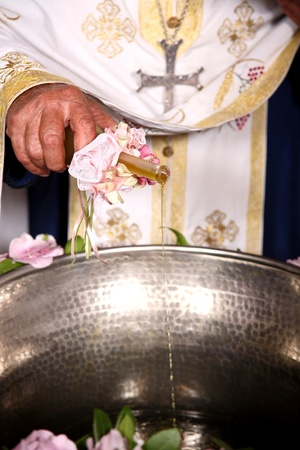 priest add oil on a bowl at an orthodox christening photo