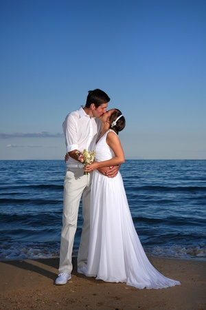 bride and groom posing at the beach after their wedding photo