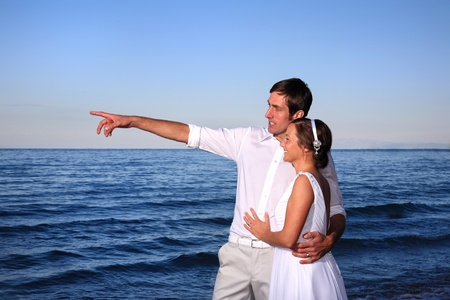bride and groom posing at the beach after their wedding Stock Photo