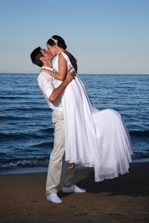couple posing at the beach after their wedding photo