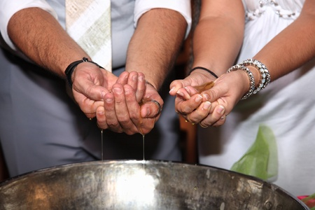 the godfather: close-up of hands with olive oil at orthodox christening