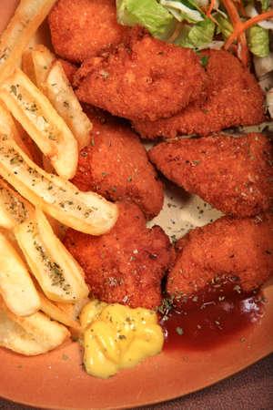 nuggets pollo: nuggets de pollo servido en un plato con salsa de tomate y ensalada de papas a la mostaza