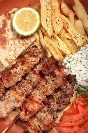 prepared food: pork skewers served on a plate with fries tzatziki pita and tomato in a greek style Stock Photo