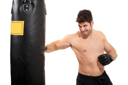 young boxer exercising on a boxing bag isolated on a white background photo