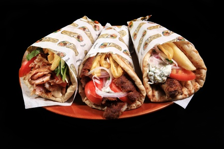 chicken lamb and pork rolled on a pita bread isolated on a black background photo