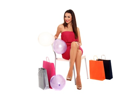 seated girl with balloons and shopping bags isolated on a white background photo