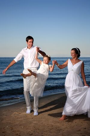 bride and groom with their kid at the beach photo