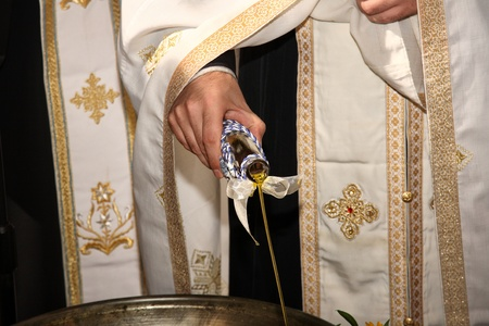 priest add oil on a christening bowl as a part of the orthodox ceremony photo