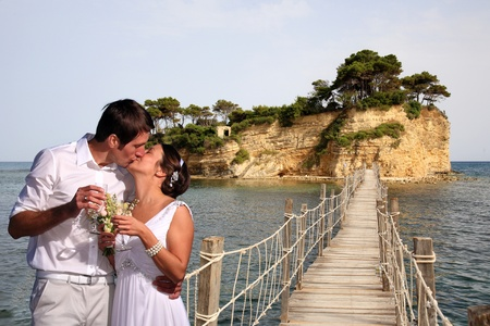 bride and groom on a bridge that connects an island