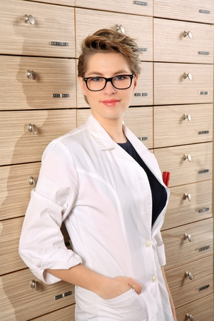 girl pharmacist portrait in front of drawers photo