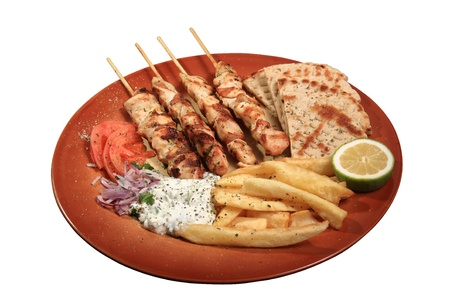 chicken skewers served on a plate with fries tzatziki and pita