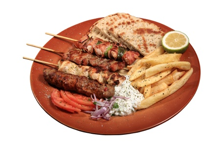 mix grill of skewers served on a plate with pita fries and tzatziki