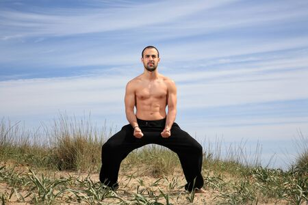 young male fighter exercising on a sand hill Stock Photo - 13577462