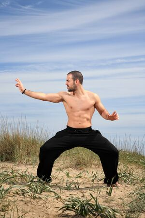 young male fighter exercising on a sand hill Stock Photo - 13577448