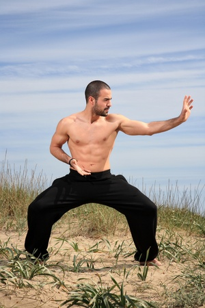 tae kwon do: young male fighter exercising on a sand hill