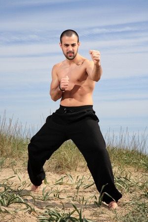 young male fighter exercising on a sand hill photo