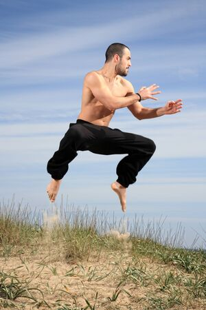 young male fighter exercising on a sand hill Stock Photo - 13577412