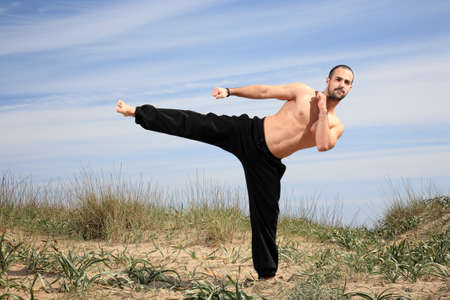 young male fighter exercising on a sand hill Stock Photo - 13577458
