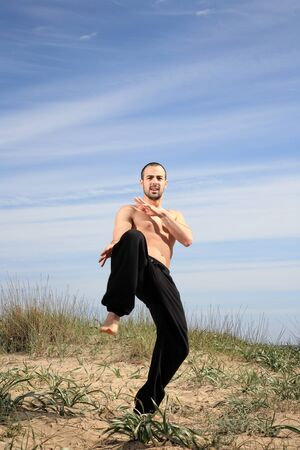 young male fighter exercising on a sand hill Stock Photo - 13577464