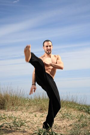 young male fighter exercising on a sand hill Stock Photo - 13577418