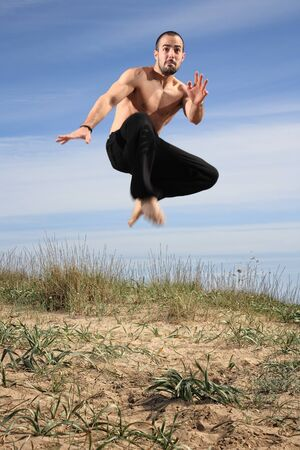 young male fighter exercising on a sand hill motion blur Stock Photo - 13577305