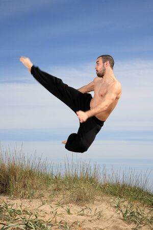 young male fighter exercising on a sand hill