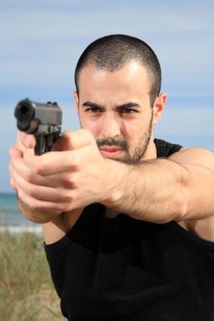 young male bodyguard holding a gun selective focus photo