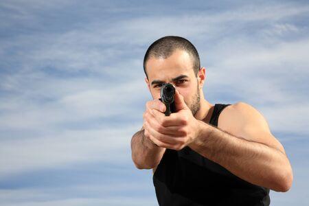 pointing gun: young male bodyguard holding a gun