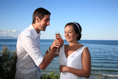 bride and groom cross hands with champagne photo