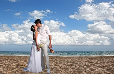 bride and groom kissing at the beach photo