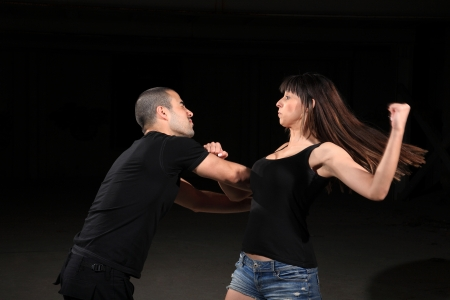 attacker: martial arts female instructor exercising with young man