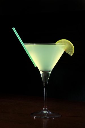 appletini cocktail with lime wheel, vodka, pineapple juice, liqueur in classic martini cocktail glass