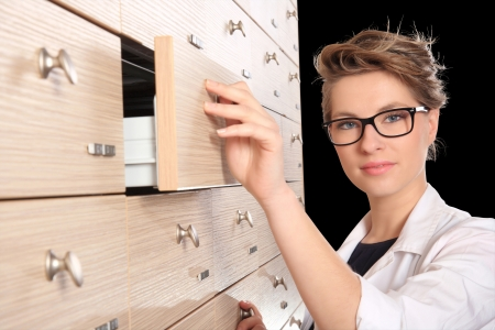girl pharmacist portrait in front of drawers isolated on a black background photo