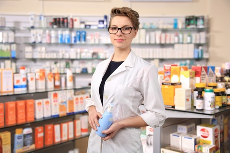 young female pharmacist holding a bottle of cream photo